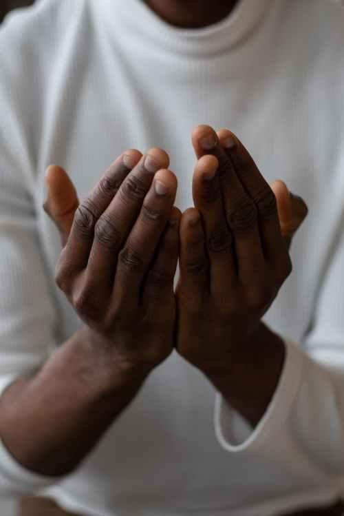 crop black man showing pray gesture