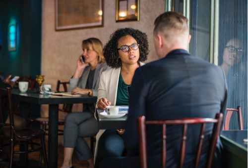man wearing suit jacket sitting on chair in front of woman wearing eyeglasses